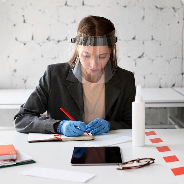 Retrato de mujer que trabaja con protector facial