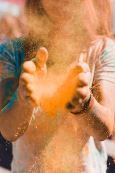Retrato de una mujer quitando el polvo del holi con las manos