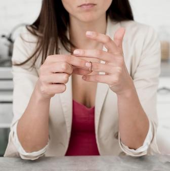Retrato de mujer quitándose su anillo de bodas