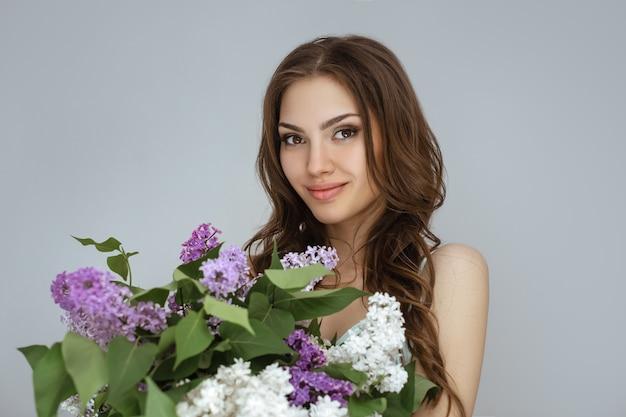 Retrato de la mujer con un ramo de flores de primavera