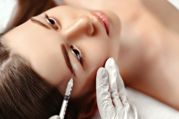 Retrato de mujer recibiendo inyección cosmética