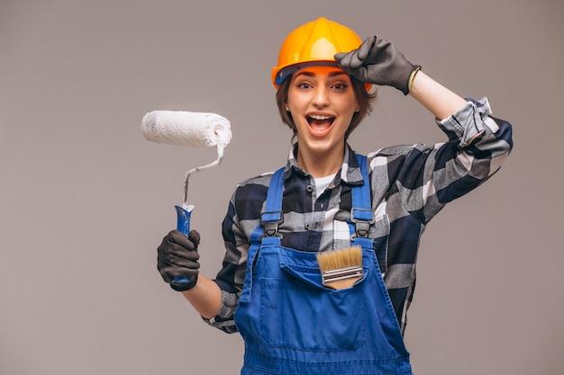 Retrato de la mujer del reparador con el rodillo de pintura aislado