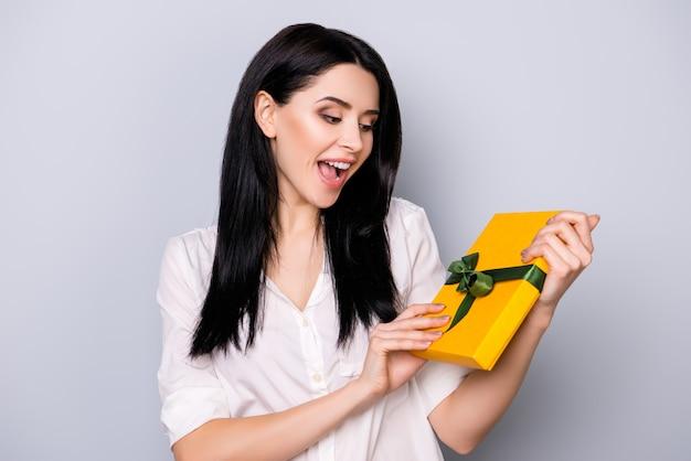 Retrato de mujer riendo bastante joven sosteniendo presente debido a su cumpleaños