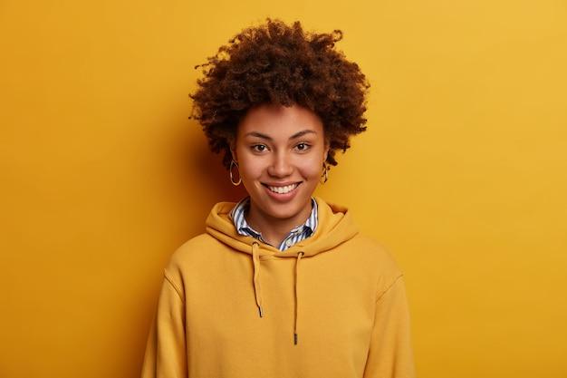 Retrato de mujer rizada étnica optimista tiene un diálogo o conversación agradable, sonríe alegremente, sudadera amarilla de guerras