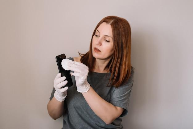 Retrato de mujer está rociando alcohol, spray desinfectante en el teléfono móvil