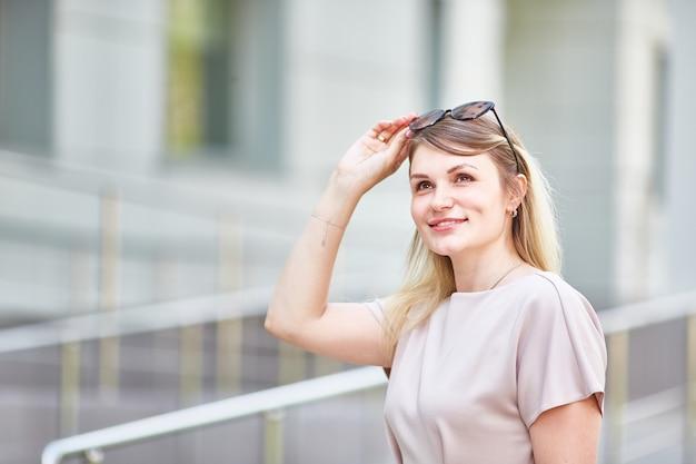 Retrato de una mujer romántica con gafas de sol que sonríe sinceramente en un día soleado en primavera.