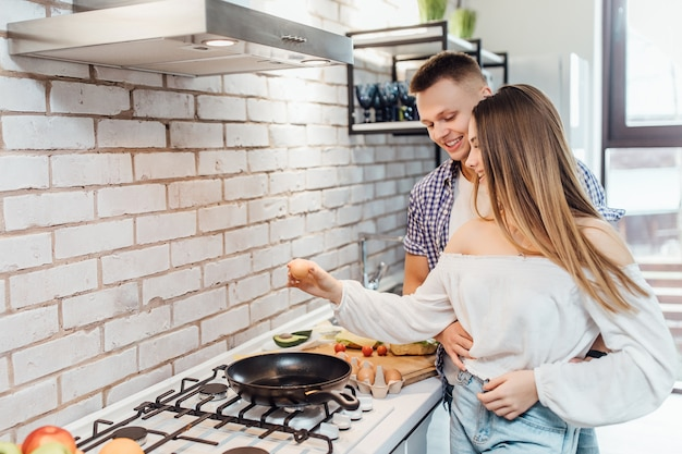 Retrato de mujer romperá un huevo sobre una sartén en la estufa. mujer preparando el desayuno con el hombre de pie.
