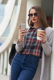 Retrato de mujer en ropa casual usando el teléfono inteligente mientras bebe café al aire libre