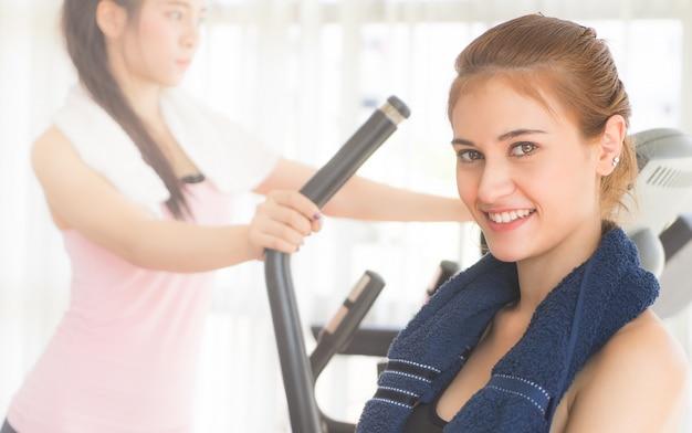 Retrato de una mujer en ropa deportiva y toalla entrenando con un amigo