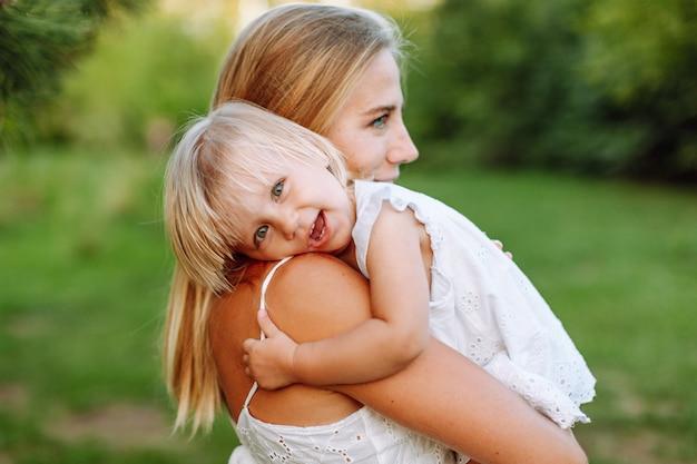 Retrato de mujer rubia abrazando a su pequeña hija en el parque de verano. chicas con vestidos blancos, aspecto familiar.
