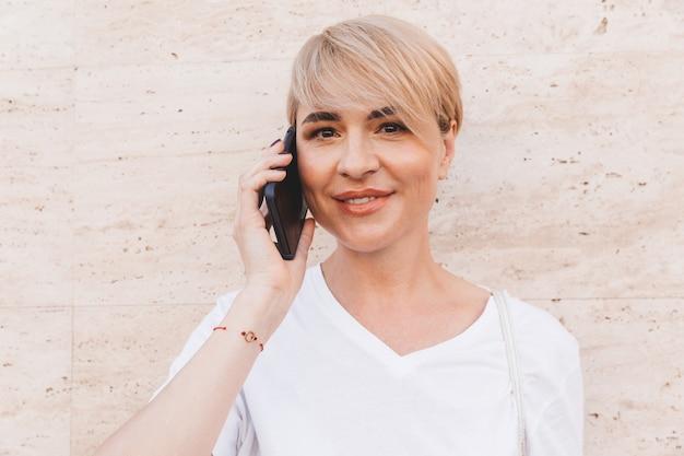 Retrato de mujer rubia alegre con camiseta blanca hablando por teléfono móvil, mientras está de pie contra la pared beige al aire libre en verano y tomando café de la taza de papel