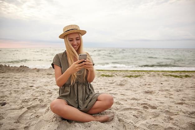 Retrato de mujer rubia atractiva con peinado casual sentada junto al mar con las piernas cruzadas, manteniendo el teléfono inteligente en la mano y mirando felizmente la pantalla, leyendo buenas noticias