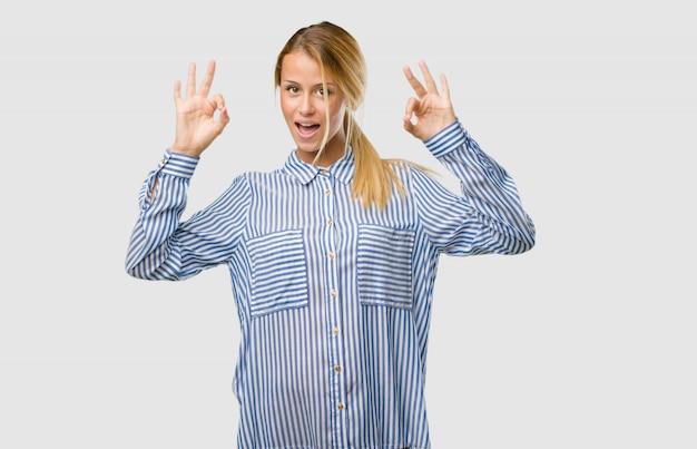 Retrato de una mujer rubia bonita joven alegre y confiada haciendo el gesto aceptable, emocionado y gritando