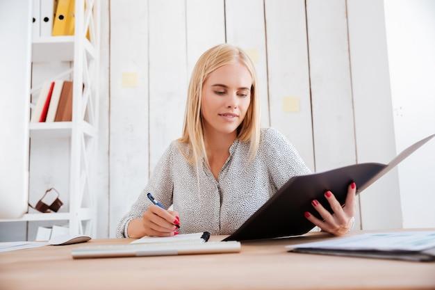 Retrato de una mujer rubia concentrada sosteniendo la carpeta abierta y haciendo notas