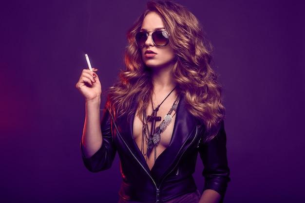 Retrato de mujer rubia elegante en gafas fumando un cigarrillo