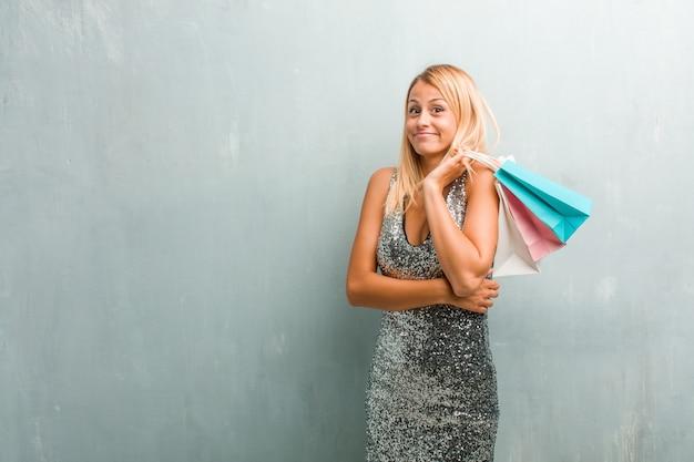 Retrato de una mujer rubia elegante joven que duda y que encoge hombros, concepto de indecisión e inseguridad, incierto sobre algo. sosteniendo la bolsa de compras.