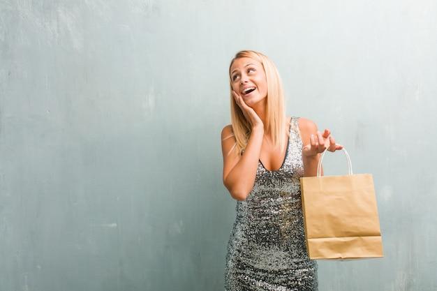 El retrato de la mujer rubia elegante joven sorprendida y conmocionada, mirando con los ojos abiertos, excitado por una oferta o por un nuevo trabajo, gana concepto. sosteniendo la bolsa de compras.