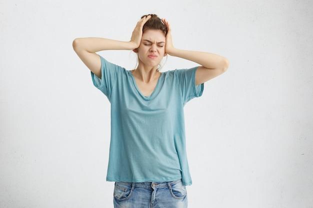 Retrato de mujer rubia estresante en ropa casual con dolor de cabeza cogidos de la mano en la cabeza frunciendo el ceño con mirada disgustada.