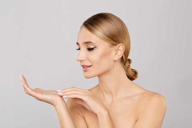 Retrato de la mujer rubia hermosa sonriente que muestra el espacio vacío de la copia en la palma abierta de la mano.
