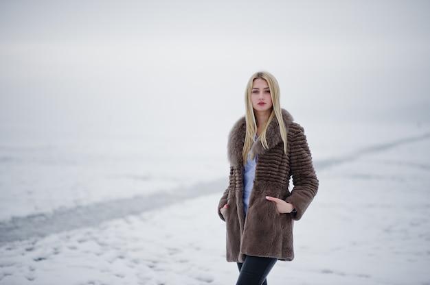 Retrato de mujer rubia joven elegancia en un abrigo de piel, río brumoso en hielo de invierno.