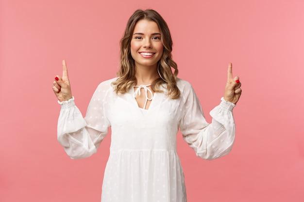 Retrato de mujer rubia joven hermosa confiada en vestido blanco lindo, señalando con el dedo hacia arriba en publicidad superior, mirando a cámara con sonrisa radiante, pared rosa de pie.