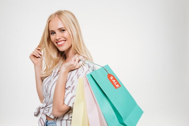 Retrato de una mujer rubia joven sonriente que sostiene el bolso de compras