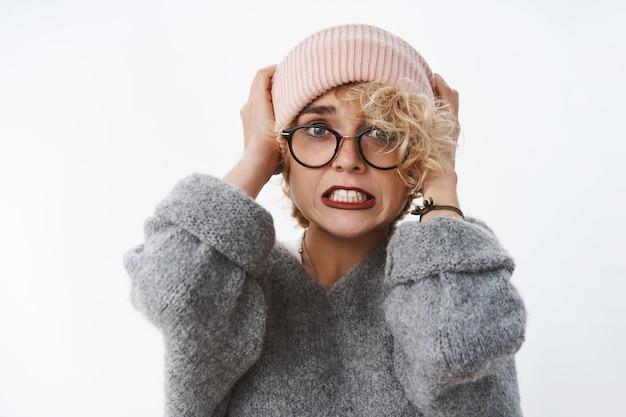 Retrato de mujer rubia linda sorprendida, disgustada y en pánico tirando gorro en la cabeza apretando los dientes con ansiedad y asustados ojos saltones preocupados por la pared blanca