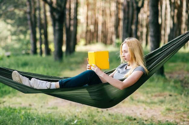 Retrato de la mujer rubia preety que se relaja en hamaca en bosque soleado y que lee el libro electrónico.