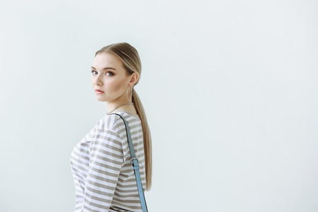 Retrato de mujer rubia en ropa casual en escena blanca con espacio libre