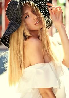 Retrato de mujer rubia sensual modelo vestida con vestido blanco y sombrero de playa de verano posando en el fondo de la calle detrás del atardecer