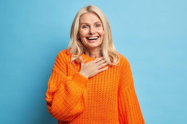Retrato de mujer rubia sincera sonríe ampliamente tiene dientes blancos perfectos mantiene la mano en el pecho se siente muy contento de recibir ayuda de una persona cercana viste suéter de punto naranja.