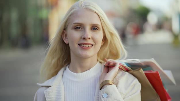 Retrato de una mujer rubia sonriente con bolsas de colores en sus manos en el fondo de una calle peatonal. concepto de tienda de compras y ropa. primer plano, 4k uhd.