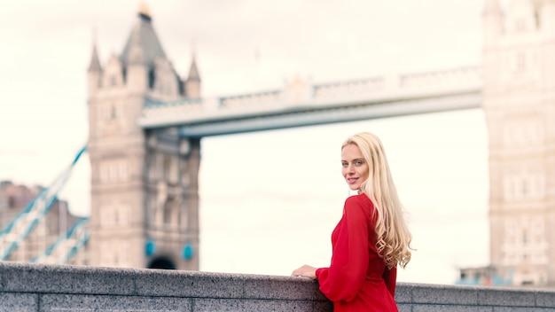 Retrato de mujer rubia sonriente en londres con el tower bridge
