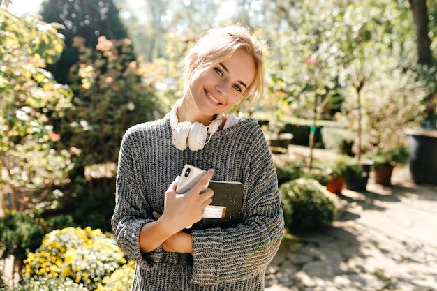 Retrato de mujer rubia sonriente en suéter de punto con teléfono y portátil en sus manos.