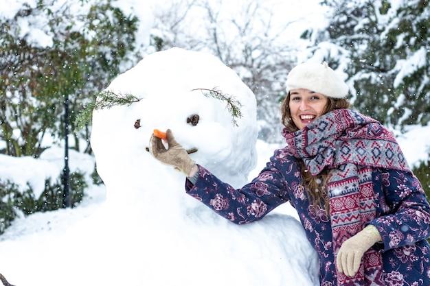 Retrato de una mujer rubia vestida con una boina, chaqueta y bufanda haciendo un muñeco de nieve.