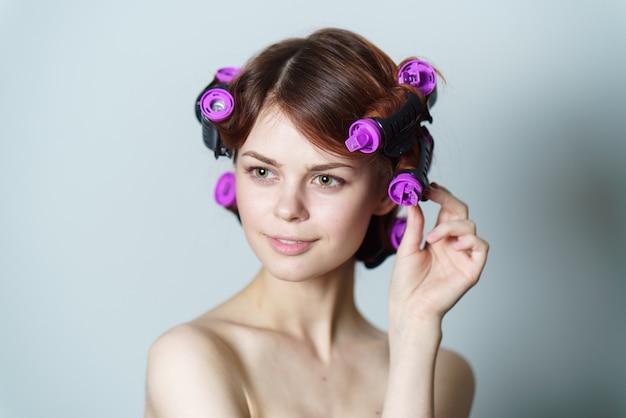 Retrato de mujer con rulos peinado casero hermoso rostro fondo claro