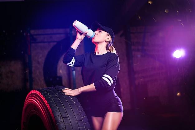Retrato de una mujer saludable fitness beber agua del agitador de botellas en el gimnasio