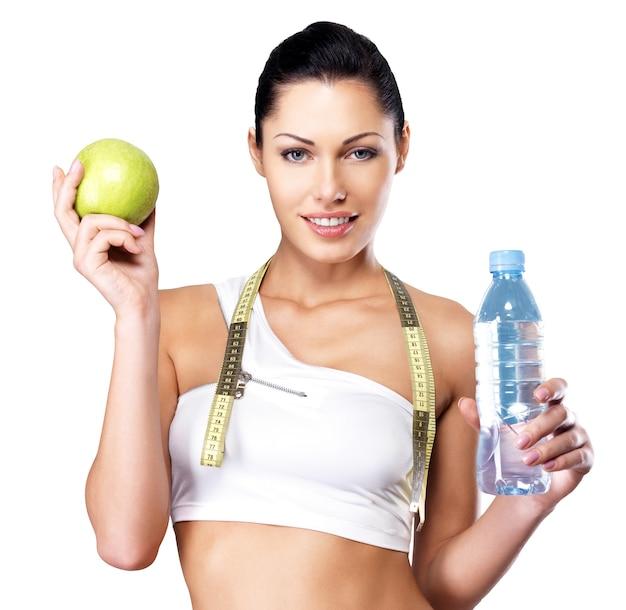 Retrato de una mujer sana con manzana y botella de agua.