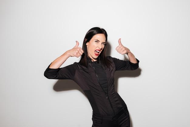 Retrato de una mujer satisfecha mostrando pulgares arriba gesto