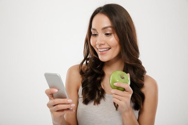 Retrato de mujer satisfecha con smartphone plateado mientras come manzana verde fresca, aislada sobre la pared blanca