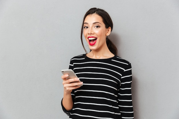Retrato de una mujer satisfecha con teléfono móvil