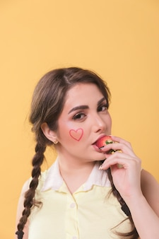 Retrato de mujer seductoramente comiendo una fresa