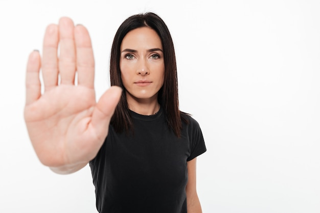 Retrato de una mujer segura mostrando gesto de parada
