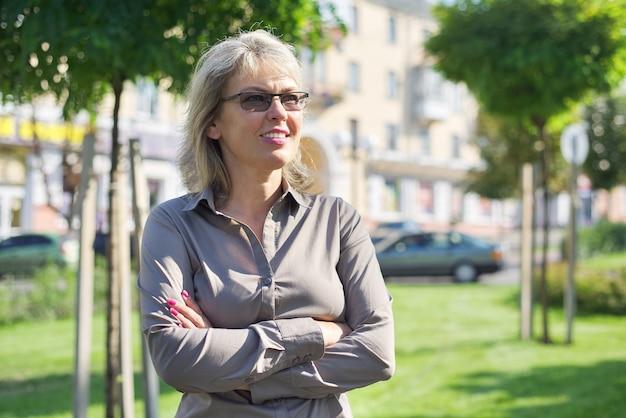 Retrato de mujer segura de negocios madura con los brazos cruzados, mujer con camisa de gafas en la ciudad