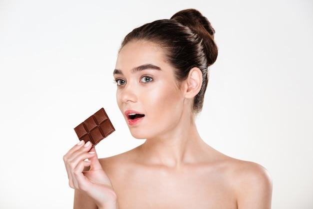Retrato de mujer semidesnuda hambrienta con cabello oscuro comiendo chocolate bar no está a dieta