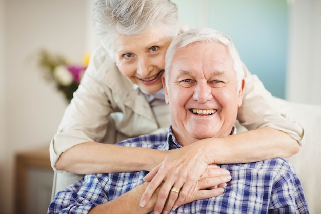 Retrato de mujer senior abrazando al hombre en la sala de estar