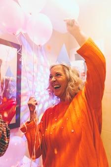 Retrato de una mujer senior feliz sosteniendo globos en la mano disfrutando en la fiesta de cumpleaños