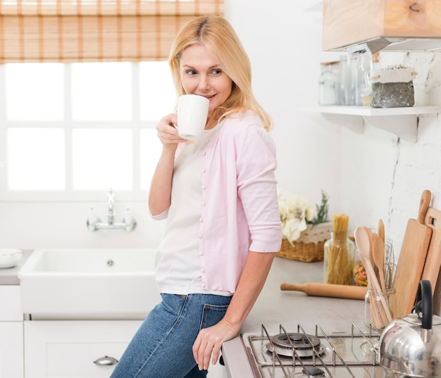 Retrato de mujer senior feliz tomando café