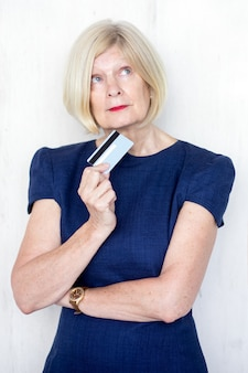 Retrato de mujer senior pensativa con tarjeta de crédito