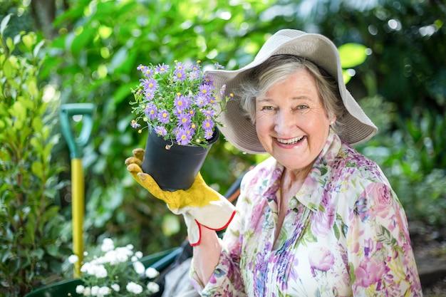 Retrato de mujer senior con planta en maceta en jardín